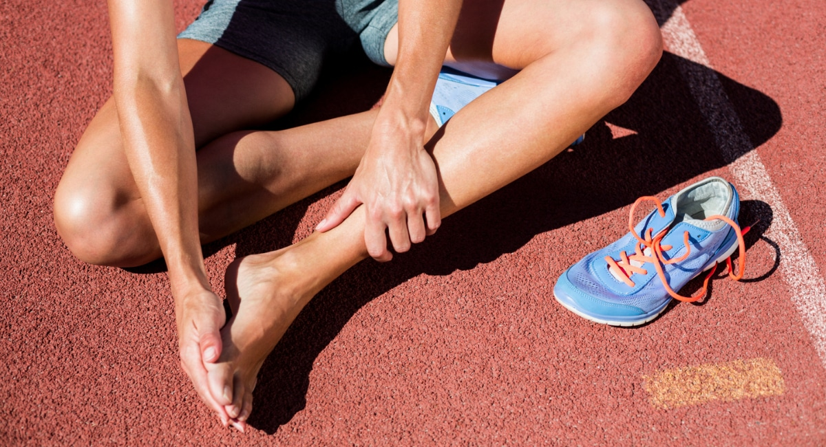 Female athlete with foot pain, sitting on track