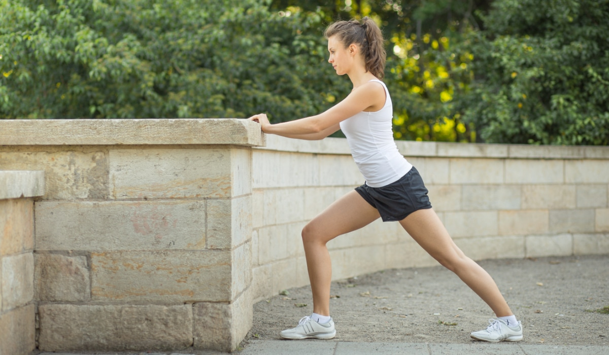 Woman stretching out calf muscles on a wall outdoors